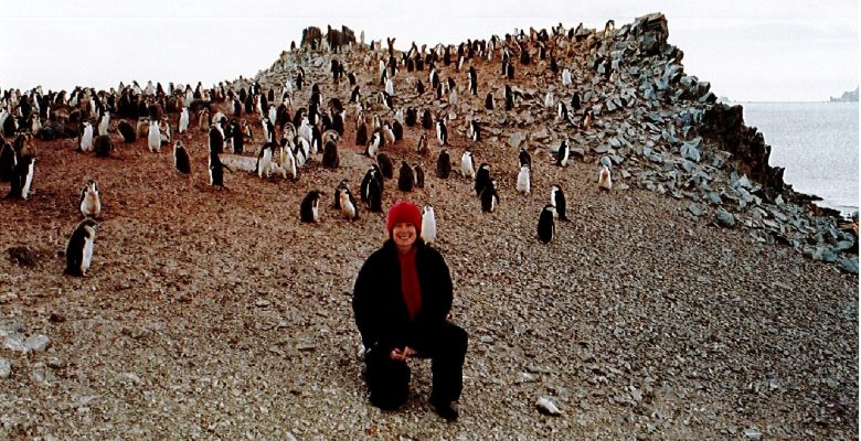Sandi Davison, PA/Administrator, with Chinstrap Penguins on Half Moon Island, Antarctica